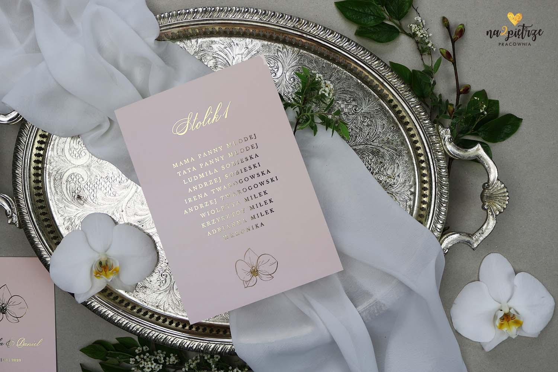 plan usadzenia gości z motywem storczyka w kolorze jasnego różu ze złotymi lieterami