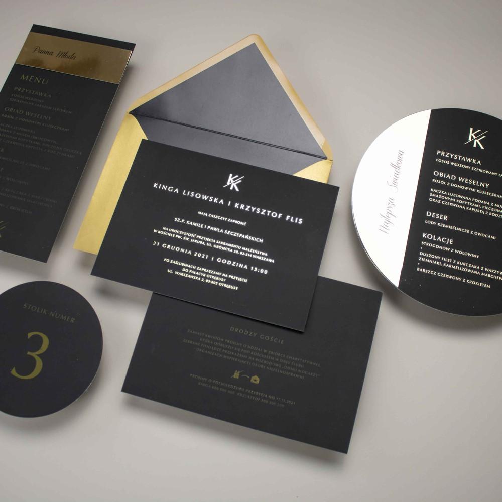 czarne zaproszenie ślubne ze złotymi literami i dodatki