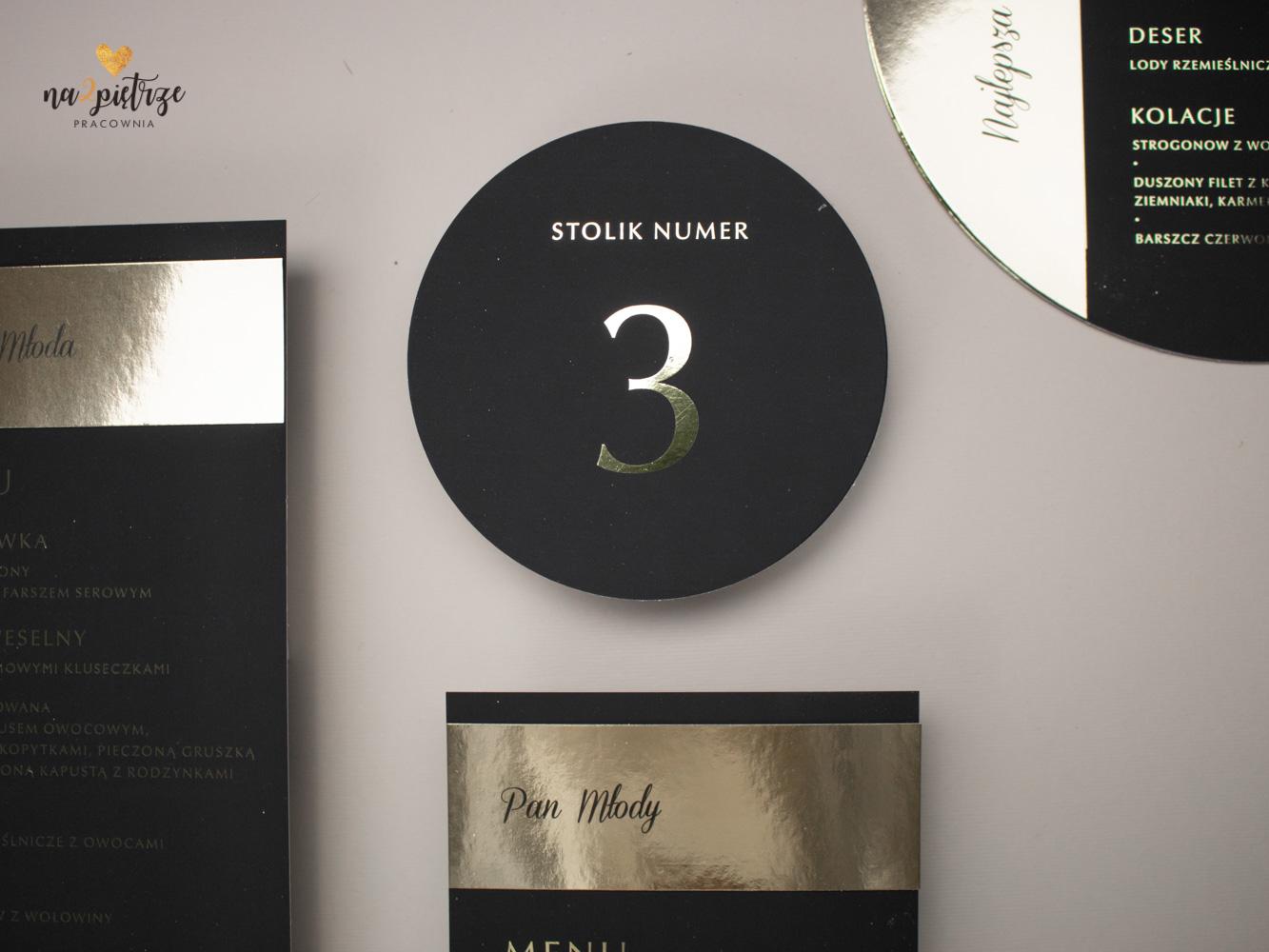 okrągły, czarny numerek stołu ze złotą cyfrą